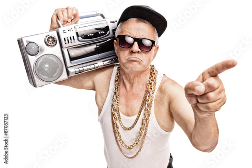 Fotografie, Obraz  Senior rapper carrying a ghetto blaster on his shoulder