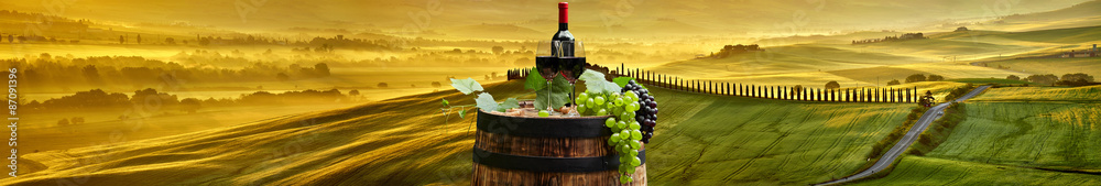 Red wine bottle and wine glass on wodden barrel. Beautiful Tusca