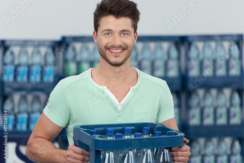 Fotografie, Obraz  mann kauft eine kiste wasser im supermarkt