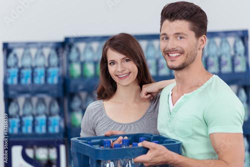 Valokuva  paar kauft eine kiste wasser im getränkemarkt
