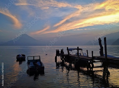 Wall Murals Coloful Sunset with dock on a lake with volcanoes