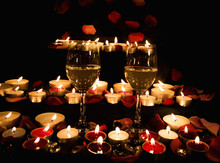 Wine Glasses, Candles And Petals Of Roses