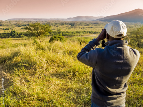Fotografía  South Africa, ranger looking through binoculars in search of animals during a sa