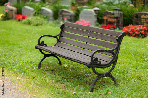 Foto op Canvas Begraafplaats Empty old wooden bench in cemetery