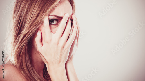 Fotomural Afraid frightened woman peeking through her fingers