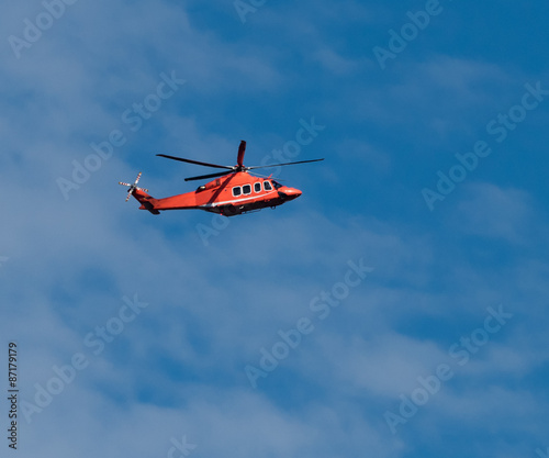 Foto op Canvas Helicopter Orange helicopter in flight on Blue Sky