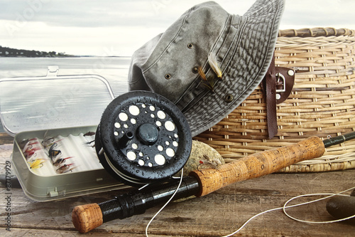 Foto op Canvas Vissen Hat and fly fishing gear on table near the water