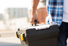 Close Up Of Builder Carrying Toolbox Outdoors
