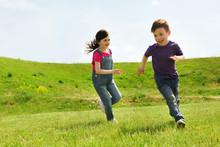 Happy Little Boy And Girl Runn...