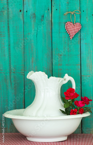 Fotografie, Obraz  Antique water pitcher and basin with red roses by rustic green background
