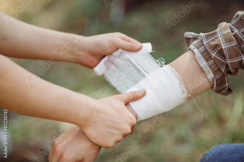 A person wrapping his friends arm in gauze Fototapet