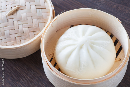 Traditional chinese cuisines steamed bun in asian style bamboo basket Poster