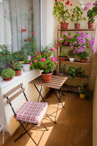Fotografie, Obraz  Beautiful balcony with small table, chair and flowers.