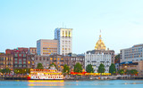 Fototapeta Sawanna - Savannah Georgia USA, skyline of historic downtown at sunset with illuminated buildings and steam boats