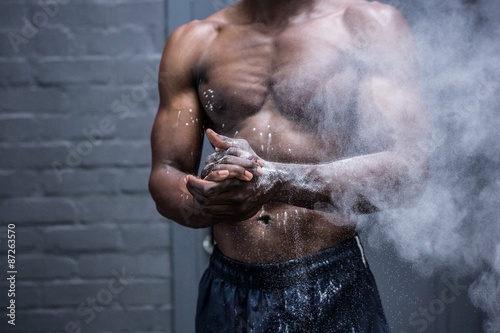 Fotografie, Obraz  Young Bodybuilder shaking Chalk off his hands
