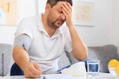 Fotografia  Man measuring  his blood pressure feeling sick.