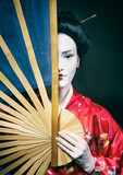 Woman in geisha makeup covering half of her face with a big fan