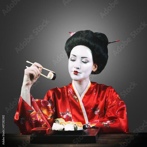 Cuadros en Lienzo Woman in geisha makeup eating sushi