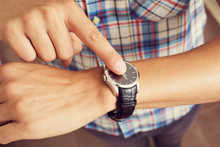 Young Man Tapping His Finger On His Wristwatch