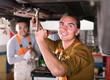 Serviceman repairing exhaust system