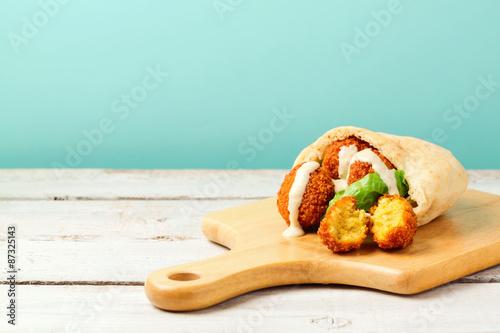 Falafel balls in pita with tahini sauce on wooden board