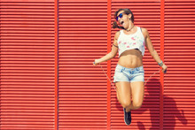 Woman Jumping Rope On Red Background