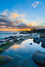 Stones In Ocean Water At Sunset Time In Playa Blanca On Lanzarote Island, Spain