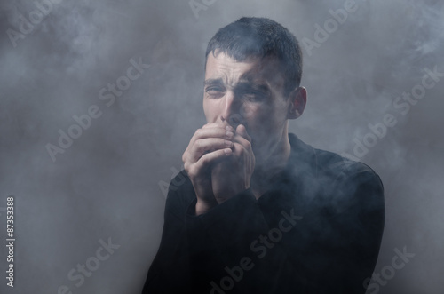 Valokuva  young man suffocating in the poisonous smoke