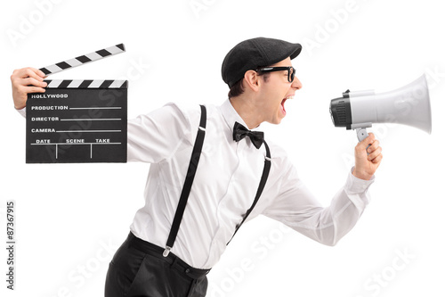 Young movie director holding a clapperboard and shouting on a me Canvas Print