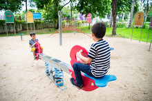 Little Boys Playing Seesaw Tog...