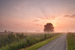 misty summer sunrise over bike road