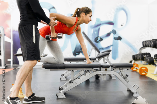 Young male trainer giving instructions to a woman in a gym Fotobehang