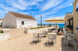Restaurant tables and white church on coastal promenade in Armacao de Pera seaside town, Portugal