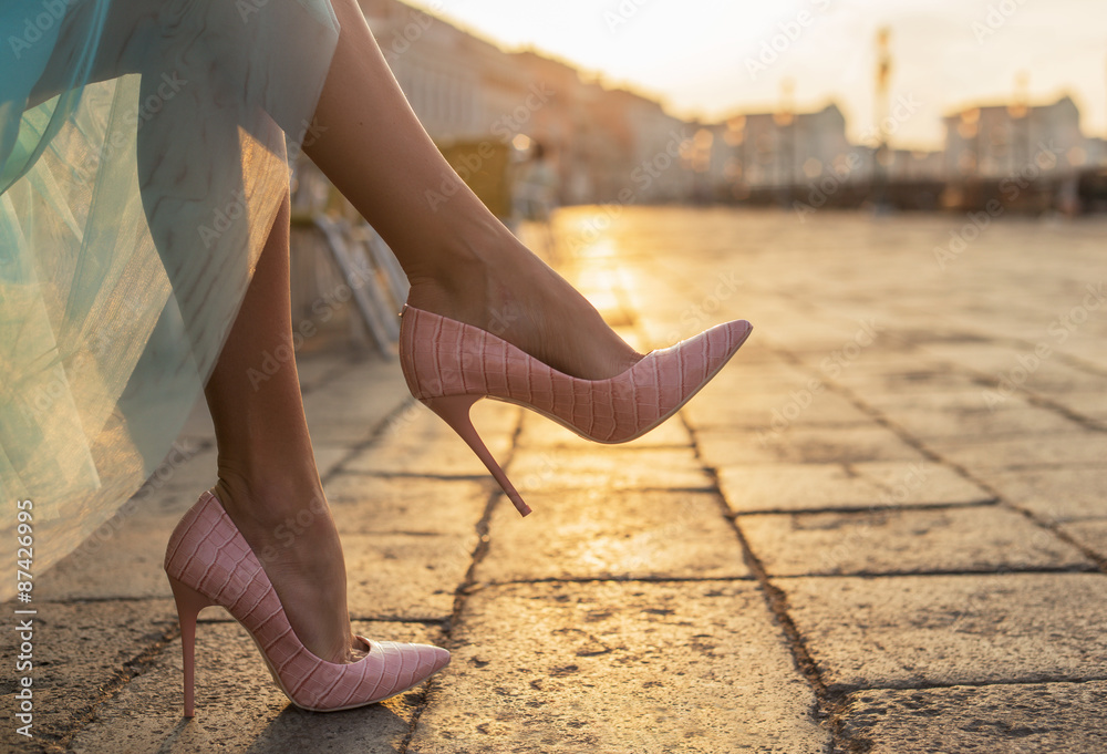 Fototapeta Woman in high heel shoes in city by sunrise