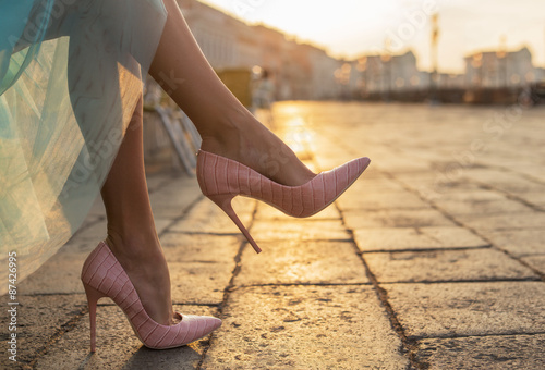 Woman in high heel shoes in city by sunrise Fototapet