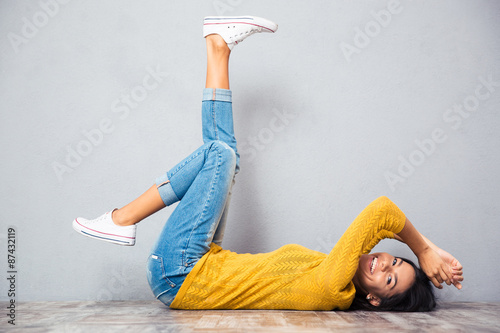 Fotografie, Obraz  Woman lying on the floor with raised legs up