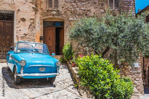 Naklejka premium Stare niebieskie środki transportu w średniowiecznym mieście we Włoszech