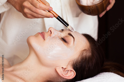 Poster  Spa treatment. Beautiful woman with facial mask at beauty salon.