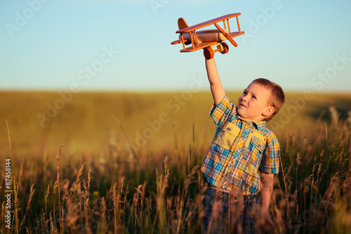 Fotografía  small boy playing with plane on meadow