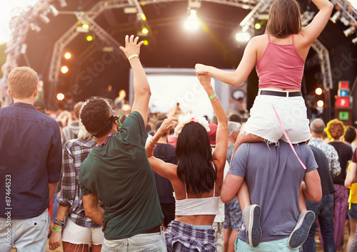 Obraz Friends having fun in the crowd at music festival, back view - fototapety do salonu