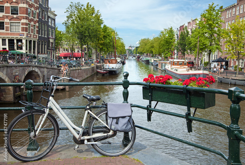 White Bicycle on a Bridge Overlooking a Canal in Amsterdam against Blue Sky Canvas