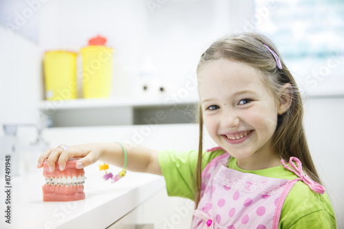 Stampa su Tela Girl holding model of human jaw with dental braces