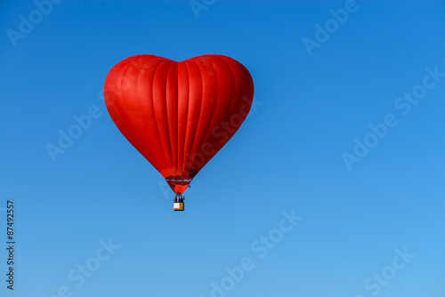 Ingelijste posters Ballon red balloon in the shape of a heart against the blue sky