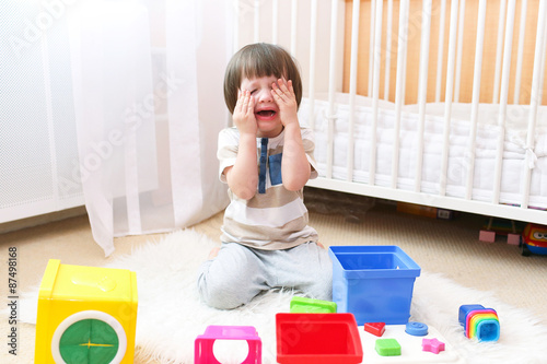 Valokuva  Crying child scatters toys at home