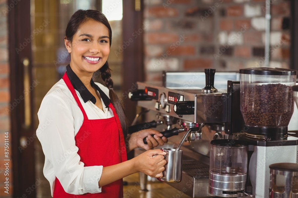 Fototapeta Smiling barista steaming milk at the coffee machine