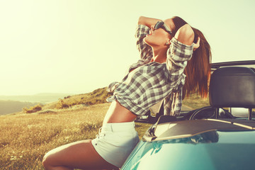 Fototapeta Samochody Attractive young woman posing leaning on convertible car at suns