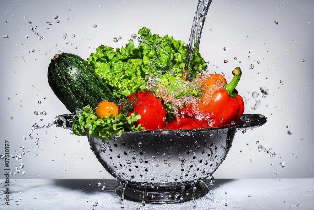 vegetables in a colander under running water