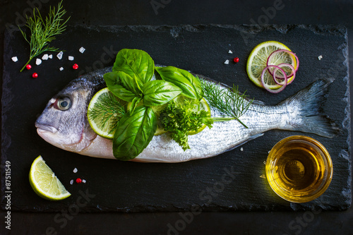 Photo  fresh raw dorado fish with spices and herbs