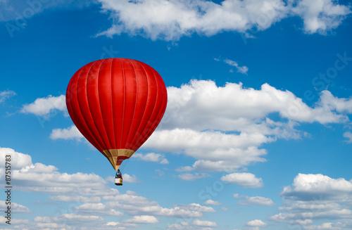 Fotografía  Red hot air balloon in blue cloudy sky