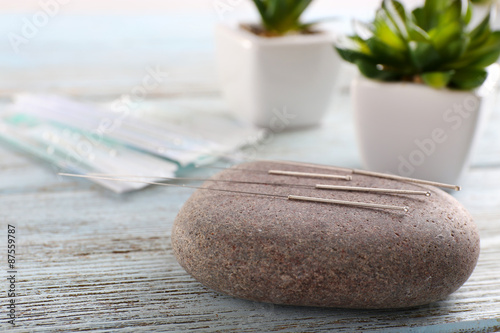 Photo Acupuncture needles with spa stone on wooden table, closeup
